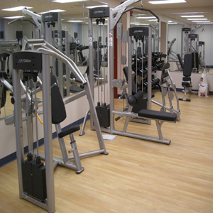 exercise equipment on wooden flooring with mirrors